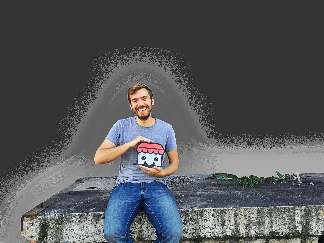 Gründer Paul sitzt auf einem Betonklotz